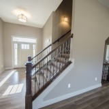 Custom stairway off entry by Design Homes.