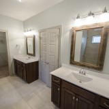Custom master bathroom with his and hers vanities by Design Homes.
