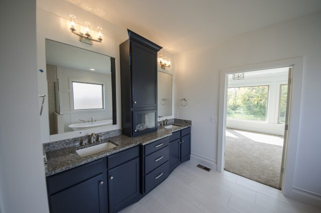 Custom master bathroom with built-in mirrors by Design Homes.