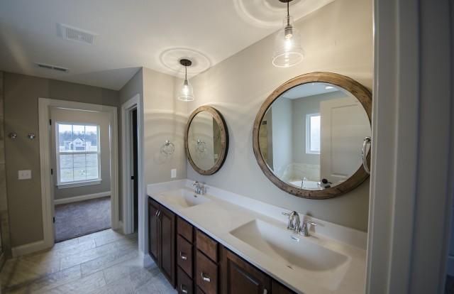 Custom master bathroom by Design Homes, custom home builder, with a round mirror.
