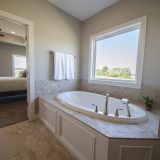 Custom master bathroom of The Triple Crown (Lot 163) in Cypress Ridge. A move-in ready home by Design Homes and Development.