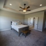 Custom master bedroom of The Triple Crown (Lot 163) in Cypress Ridge. A move-in ready home by Design Homes and Development.